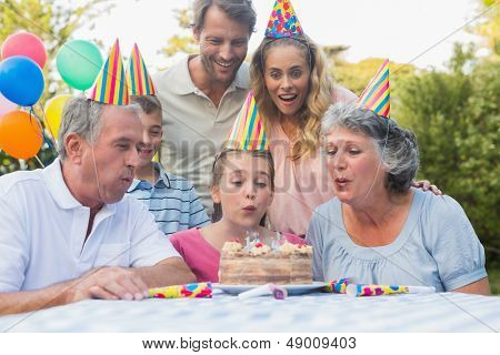 Cheerful extended family watching girl blowing out birthday candles outside at picnic table
