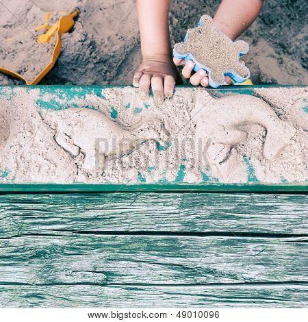 Kid Creating Animal Forms In Sandpit