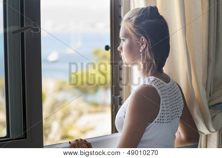 young woman is near the window
