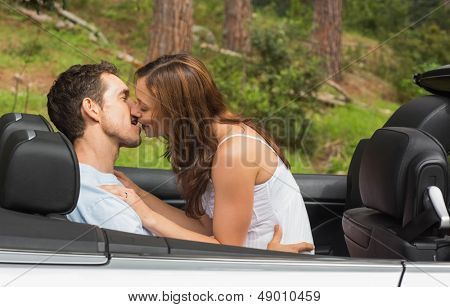 Young couple smooching on the backseat of a convertible