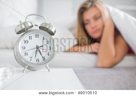 Tired blonde staring at her alarm clock at home in bedroom