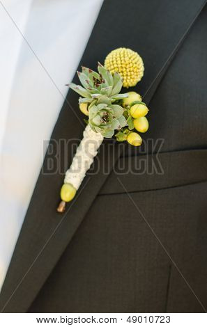 Groomsmen in black wedding suits wearing rose boutonnieres