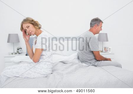 Annoyed couple sitting on different sides of bed having a dispute with woman looking at camera in bedroom at home