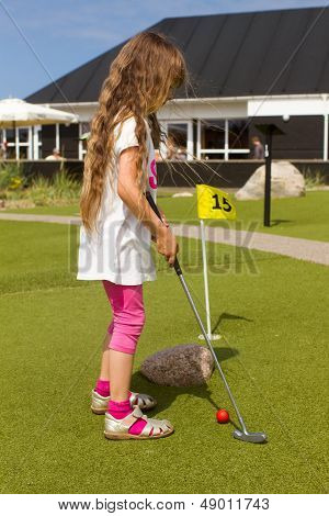Young Long-haired Girl Playing Minigolf