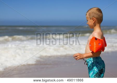 Boy With Orange Water Wings At Beach