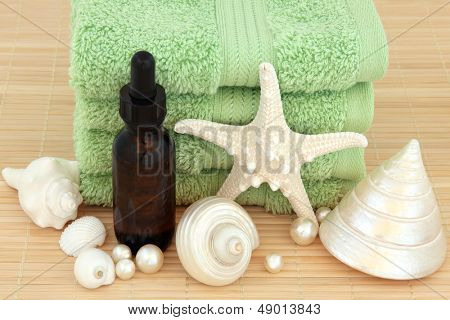Aromatherapy essential oil bottle with green towels, sea shell selection and pearls over bamboo background.