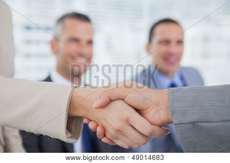 Future workmates shaking hands in bright office