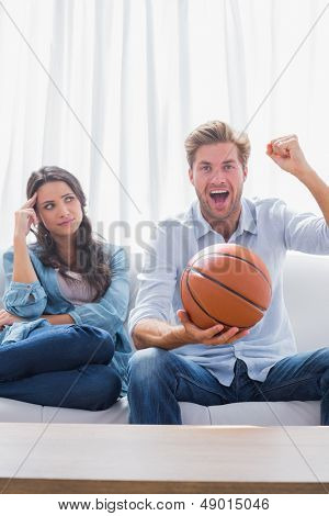 Woman looking at her husband cheering the basketball game at home on couch