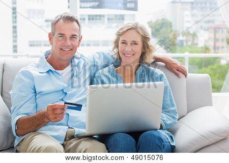 Casal feliz sentado no sofá deles usando o laptop para comprar on-line sorrindo para a câmera em casa na