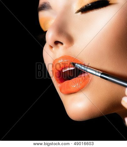 Makeup Applying. Professional Make-up. Lipgloss brush. Lipstick. Beauty Fashion Girl Applying Orange Lipgloss. Isolated on black background
