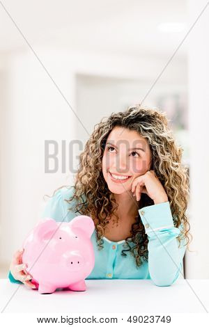 Thoughtful woman with her savings in a piggybank