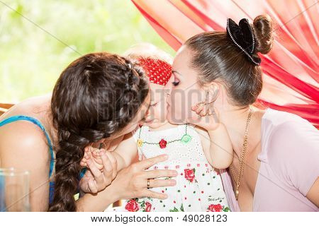 Happy Mom And Godmother Kissing Baby Girl . The Concept Of Childhood And Family.