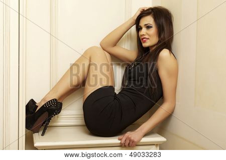 Beautiful and attractive young adult female brunette sensuality woman posing in black dress in apartment