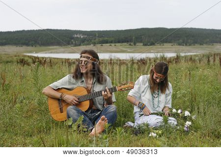 Hippie Men Play On The Guitar And Woman Make A Wreath