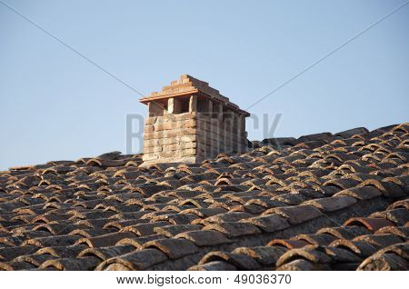 A tiled roof with a chimney