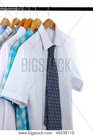 Camisas com laços em cabides de madeira isolados no branco
