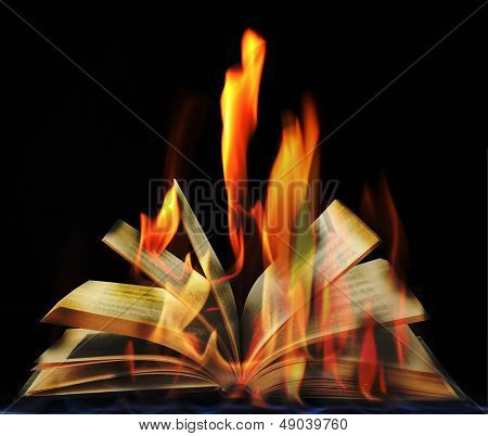 Open book in flame on black background