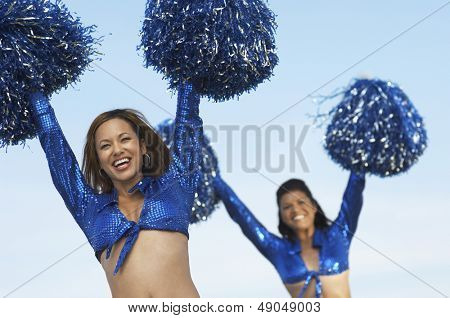 Portrait of two happy cheerleaders with pom poms raised against the sky