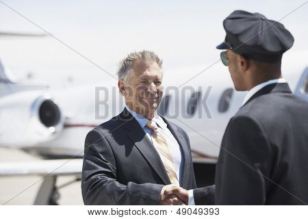 Smiling senior businessman shaking hands with pilot and blurred aircraft in the background