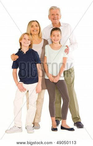 Young Grandmother And Grandfather With Nephew And Niece Standing On White Background
