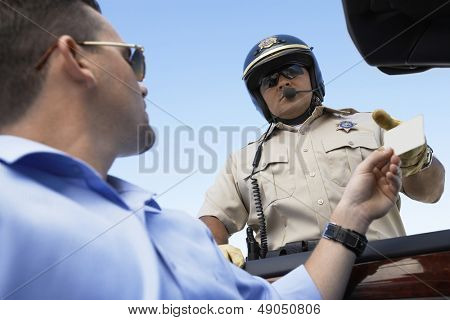 Closeup low angle view of a man handing license to police officer against clear blue sky