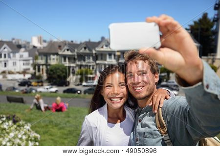 Happy young couple in San Francisco Alamo Square taking self-portrait photo pictures with smart cell phone camera. Multiethnic interracial couple tourists on sightseeing travel in California, USA