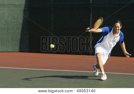 Full length of a male tennis player hitting backhand on the tennis court