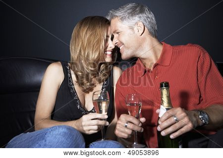 Romantic and happy couple with champagne flutes rubbing noses