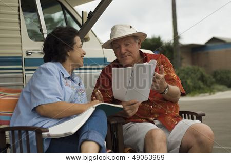 Happy middle aged couple with magazines relaxing outside their motor home