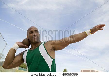 Close de uma arremessadora de peso se preparando para lançar o arremesso contra o céu