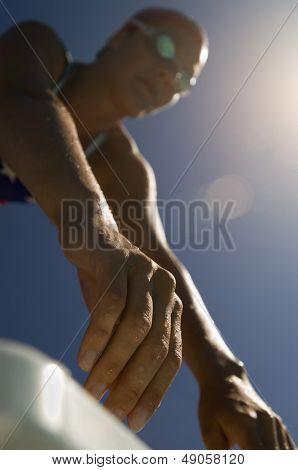 Vista de ángulo bajo de un nadador femenino en los podiums con enfoque en las manos