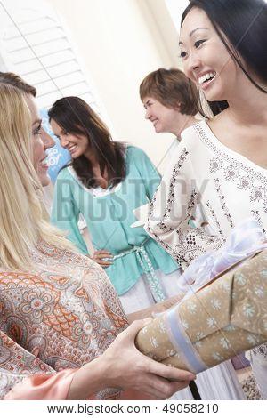 Caucasian Frau giving a Gift to schwangere asiatische Frauen auf Baby-Dusche