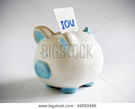 IOU note in piggy bank signifying debt or financial problems
