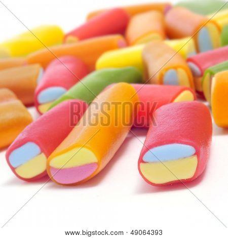primer plano de un montón de caramelos de regaliz de diversos colores sobre un fondo blanco