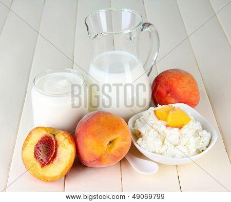 Productos lácteos frescos con duraznos en primer plano de la mesa de madera
