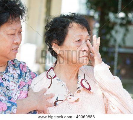 Sadness senior woman wiping off her tears in eyes, consoling by her mature daughter, natural outdoor park.