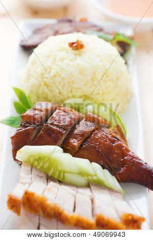 Roasted duck and roasted pork crispy siu yuk, Chinese style, served with steamed rice on dining table. Malaysia cuisine.