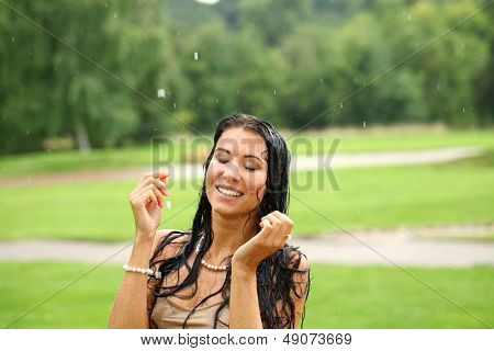 Young happy woman walking in the rain