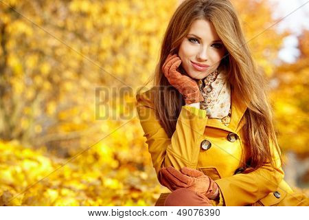 Young woman with autumn leaves in hand and fall yellow maple garden background
