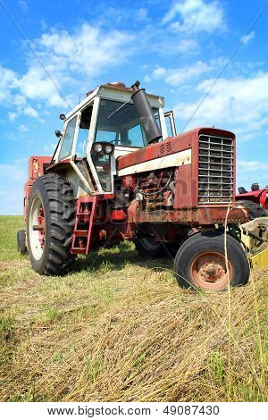 Old Farm Tractor In Grass Field