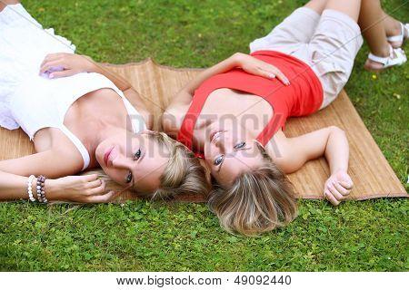 Porträt von zwei Mädchen, die ziemlich viel im Park Spaß. Sie sind reden, diskutieren, Leu