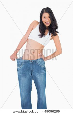 Smiling sexy woman wearing too big jeans on white background