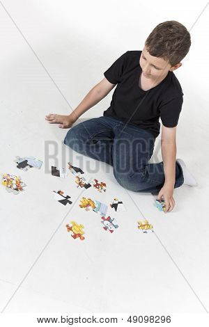 Young boy is putting puzzle together