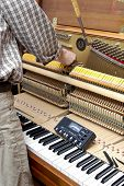 pic of tuning fork  - Detailed view of Upright Piano during tuning.Technician hand adjusting the strings of the piano.