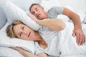 stock photo of irritated  - Irritated wife blocking her ears from noise of husband snoring in bedroom at home - JPG