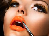 Makeup Applying. Professional Make-up. Lipgloss brush. Lipstick. Beauty Fashion Girl Applying Orange
