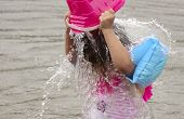 stock photo of floaties  - A young girl is dumping a bucket of water over her head while wearing arm floaties - JPG