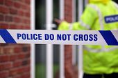 stock photo of criminology  - Crime scene investigation police do not cross boundary tape investigating policeman - JPG