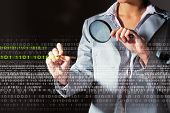 image of maliciousness  - Businesswoman with magnifier glass examining binary code - JPG