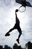 stock photo of slam  - Basketball player silhouette about to slam dunk - JPG